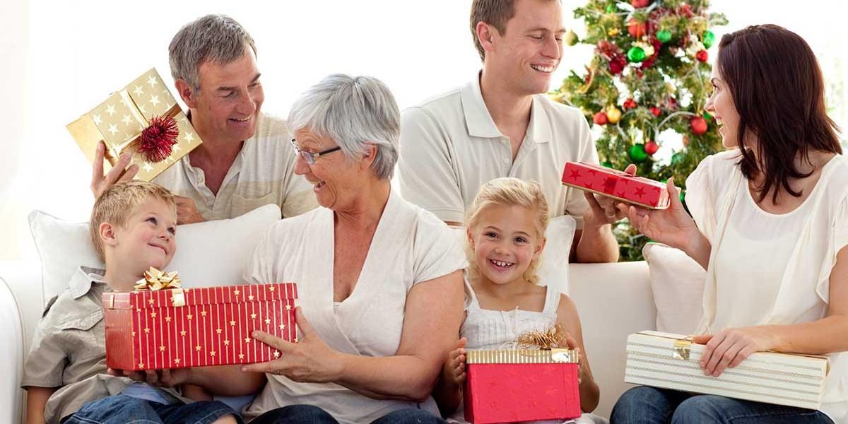 family giving presents around christmas tree
